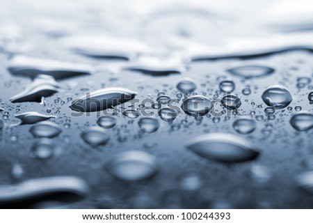 water drops on blue surface, focus in the middle, shallow depth of field