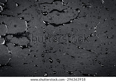 Water drops on dark stone surface of basalt or granite - stock photo