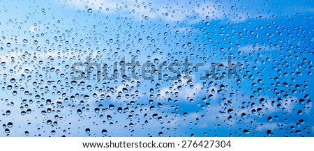 Water drops on glass against blue sky.