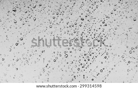 Water drops on glass against the storm sky - stock photo