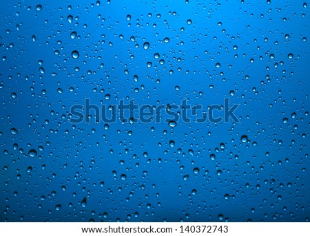 Water drops on glass and blue background