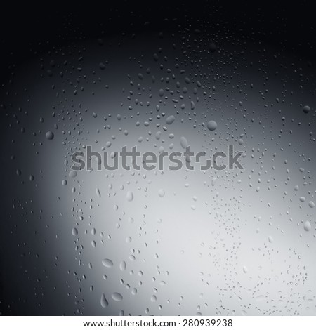 Water drops on glass behind a grey background - stock photo