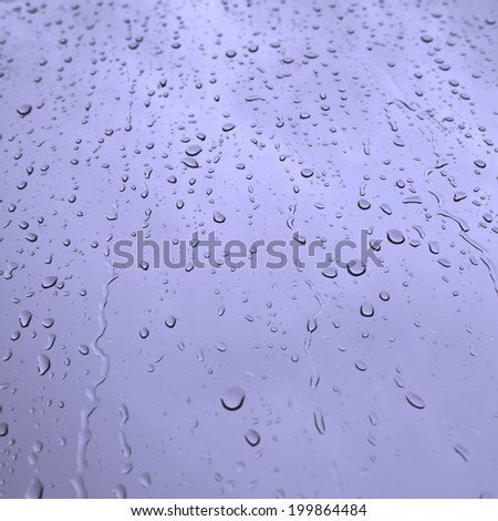 Water drops on glass in blue - stock photo