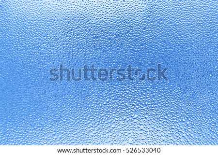 Water drops on glass, naural blue background