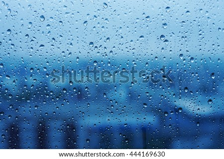 Water Drops on Glass with Blurred Cityscape View in Rainy Season