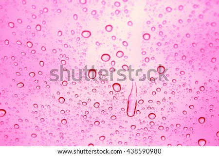 Water drops on glass with pink background - stock photo