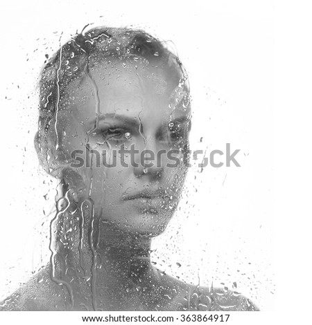 Water drops on mirror with the beautiful face of young caucasian woman. Black and white