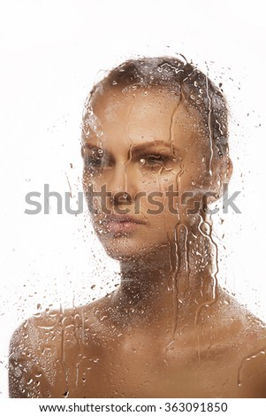 Water drops on mirror with the beautiful face of young caucasian woman. Toned - stock photo