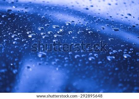 water drops on reflection blue metallic car chrome - stock photo