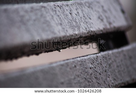 Water drops on the wet grey bench in rainy weather
