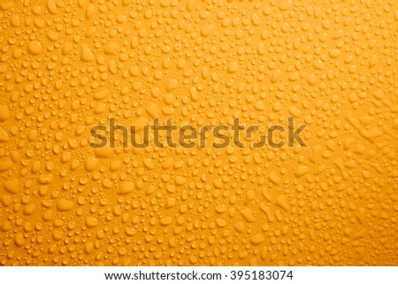 Water drops on yellow background - stock photo