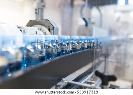 Water factory - Water bottling line for processing and bottling pure spring water into green glass small bottles. Selective focus.