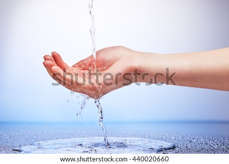 Water falling in womanâ??s hand on white and blue background