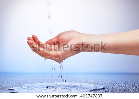 Water falling in womenâ??s hand on white and blue background