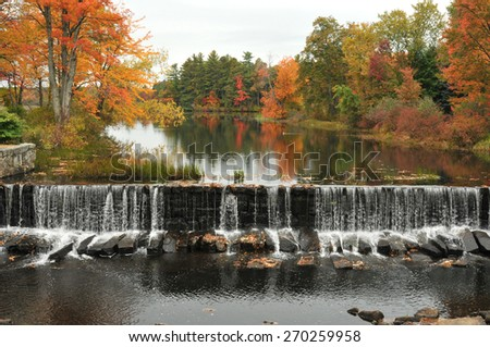 Water falling over a dam and brilliant foliage in Townsend, Massachusetts