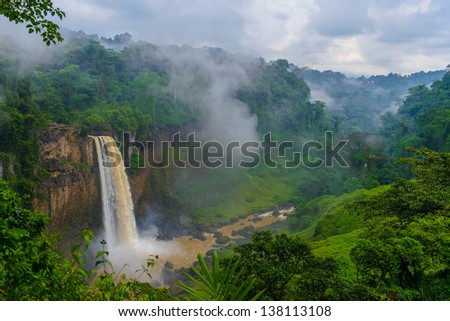 Water falls down out of the rock though the mist - stock photo