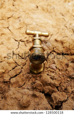 Water faucet on dry soil texture - stock photo