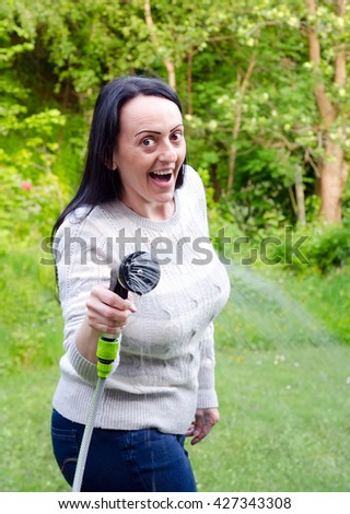 water fight, smiling, laughing woman aiming running hosepipe in garden. Portrait. - stock photo