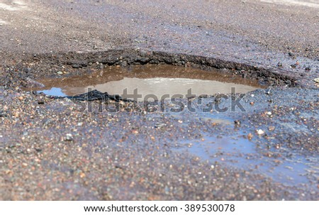Water filled pothole in a wet road. Focus is on the far wall of the pothole, which is speckled with reflected sunlight. The view is from a low angle, close to the road. There is room for text. - stock photo