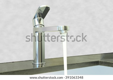 Water flow faucet granite counter on cement wall.