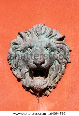 Water flow from lion statue on wall