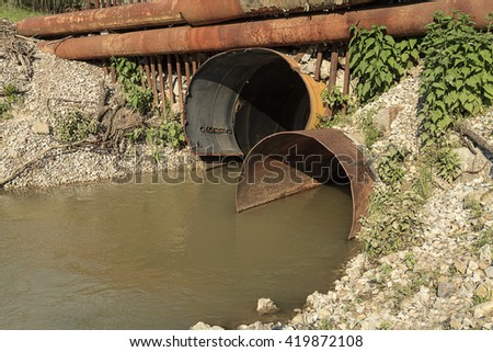 Water flow from the sewer into the river Dirty drain polluting sewer contamination danger Dirty drain polluting sewer contamination danger Dirty drain polluting sewer contamination danger Dirty drain  - stock photo