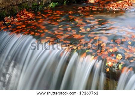Water flow in autumn scenery - long exposure - stock photo