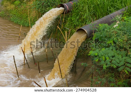 Water flow stops away from the sewer into the river, which is grass-covered coast. - stock photo