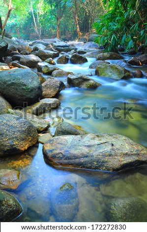 Water Flow Through Rocks In A Shallow Stream Through Malaysia Jungle - stock photo