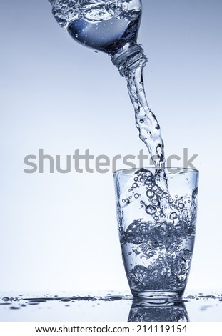 Water flowing and splashing from a plastic bottle into a glass