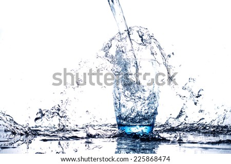 Water flowing and splashing into a glass - stock photo
