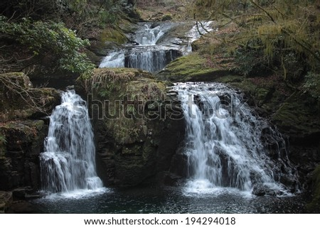 Water flowing down a hill and two waterfalls into a body of water. - stock photo