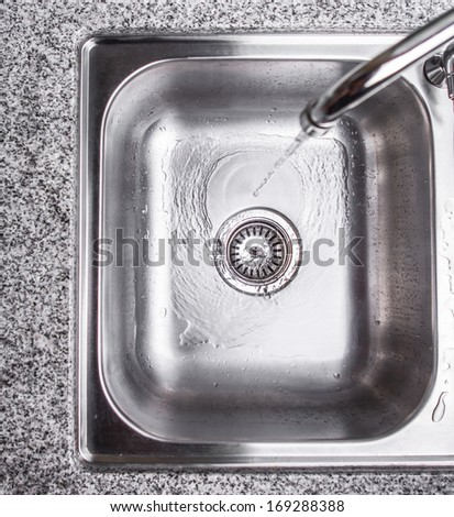 Water flowing down the hole in a kitchen sink - stock photo