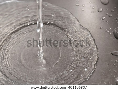 Water flowing down the hole in a kitchen sink. Selective focus.
