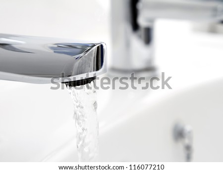 Water flowing from tap into basin - stock photo