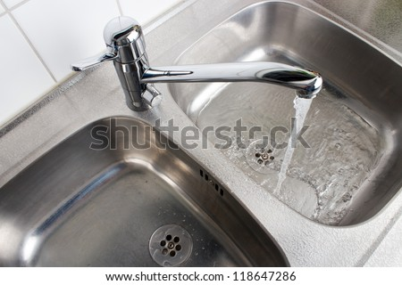 Water flowing from the faucet to the washbasin