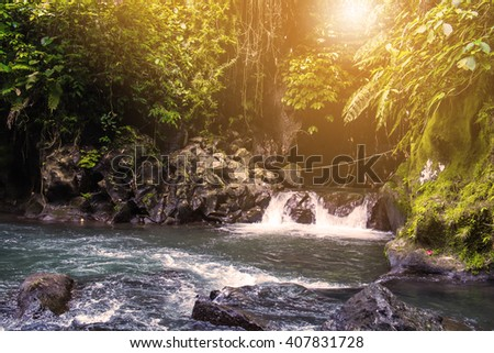 Water flowing from water fall with cave and bright sunlight in the morning - stock photo