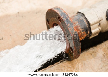 Water flowing head rusty iron tube - stock photo