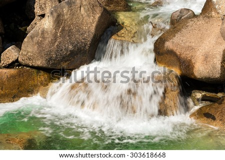 Water Flowing in the Creek / Detail of water flowing over the rocks. Long time exposure - stock photo