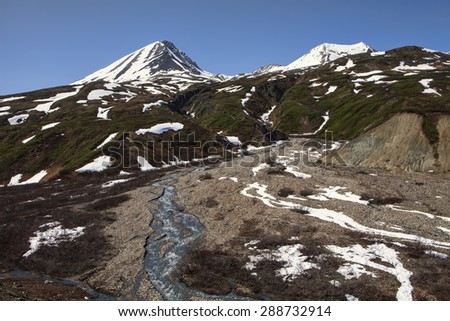 Water flowing off mountains from glacial melt and melting snow in spring in high elevations in British Columbia Canada. - stock photo