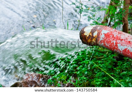Water flowing on a rusty pipe. Not potable water - stock photo