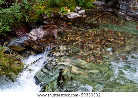 Water flowing over beautiful rocks and boulders near Baring Falls at Glacier National Park - stock photo