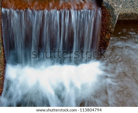 water flowing over edge of concrete wall into a pool of shallow water - stock photo