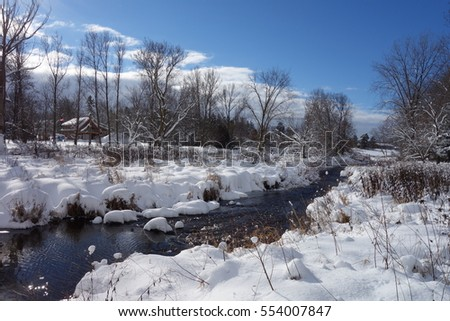 Water flows down the river surrounded by fresh snow.