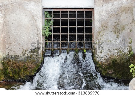 water flows from grill spring - stock photo