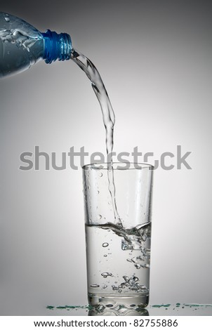 Water flows in a glass from a plastic bottle