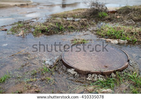 Water flows out of the manhole. The accident in the sewer. The pipe is cracked and out of water gushed out. - stock photo