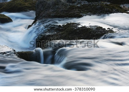 water flows smoothly over rocks  - stock photo