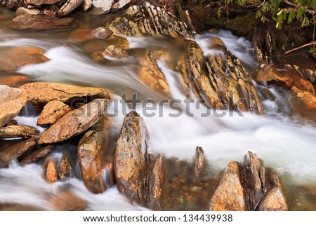 Water flows swiftly over a stream's rocky bottom in Great Smoky Mountains National Park, Tennessee, USA. - stock photo