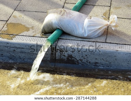 Water flows through hose pipe after being pumped from flooded building - stock photo